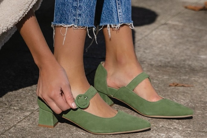 Woman wearing a pair of green shoes.