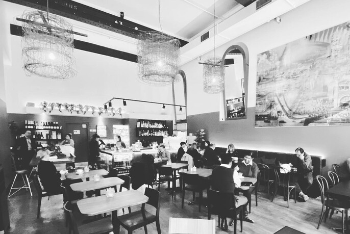 Old-style black and white image taken inside a cafe.