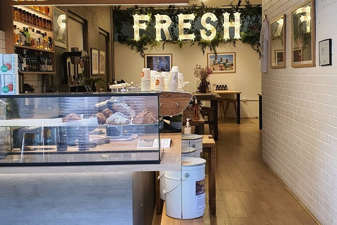 Cartel cafe interior with glass counter, shelves, tables and hanging display featuring the word 'fresh'.