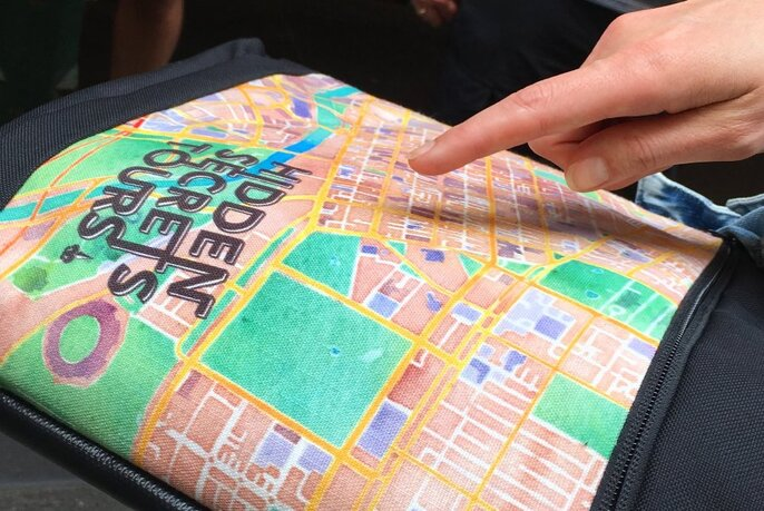 Person pointing to a Hidden Secrets Tour map.