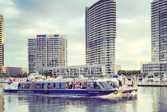 Water vessel with people on board, cruising the Yarra River with city skyline in the background.