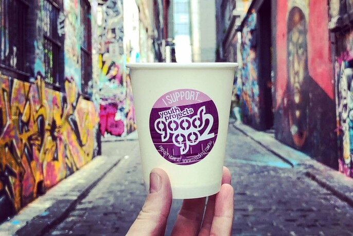 Person holding a takeaway cup with Hosier Lane street art in background.