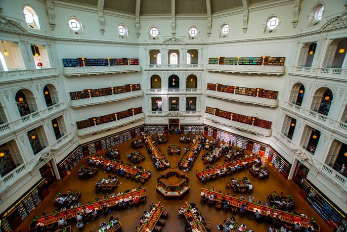 People seated at desks arranged in an octagonal pattern inside the La Trobe Reading Room of State Library Victoria.