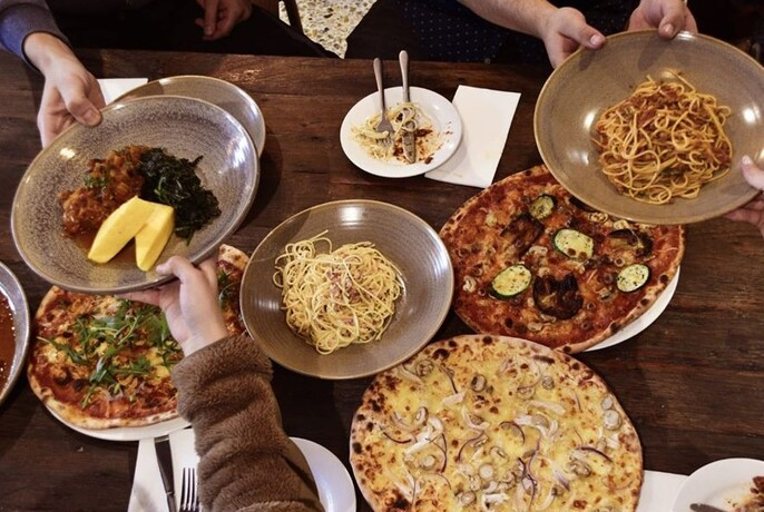 Hands holding dishes over a wooden table including pasta, pizza and meat.