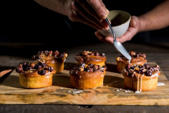 Six small pastries topped with fruit, hands above drizzling icing with a spoon.