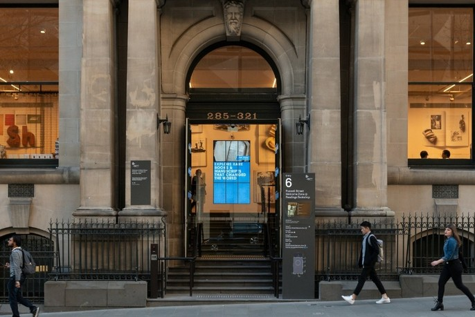 People walk past an entrance to State Library Victoria building.