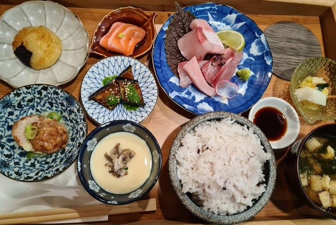 Dishes including rice, soup and meat in Japanese crockery.
