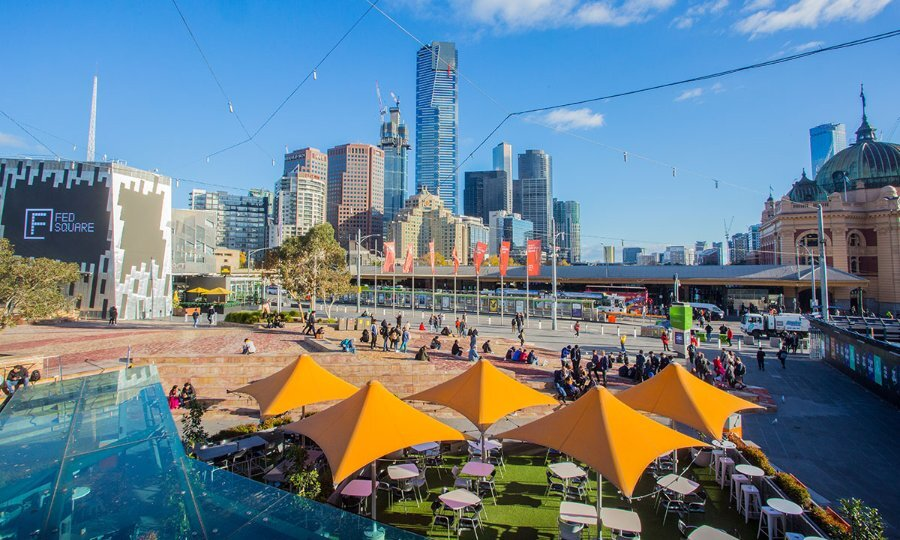 View over central Melbourne with cafe umbrellas and tall buildings in the background.