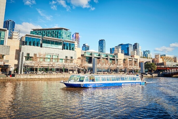 Enclosed ferry cruising the Yarra River with city skyline in the background.