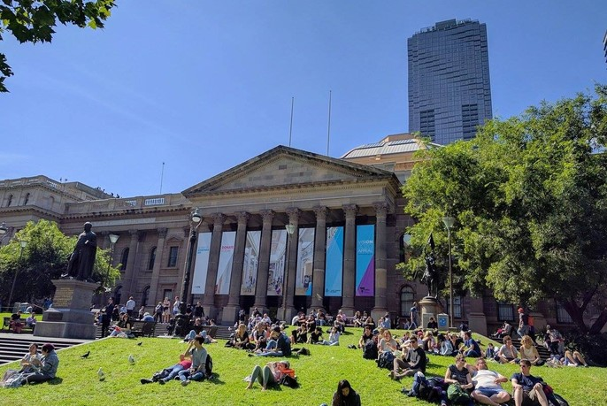 People seated on the lawn in front of the neo-classical columns and pediment of State Library Victoria.