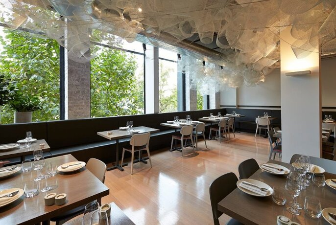 Restaurant interior with tables against large windows, floating white chiffon fabric on ceiling.