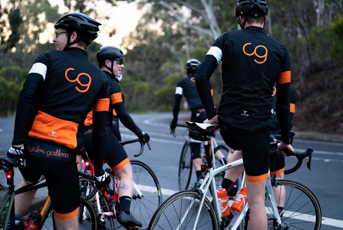 A group of men all wearing branded Cycle Galleria lycra riding gear straddling their bikes as if about to commence riding.