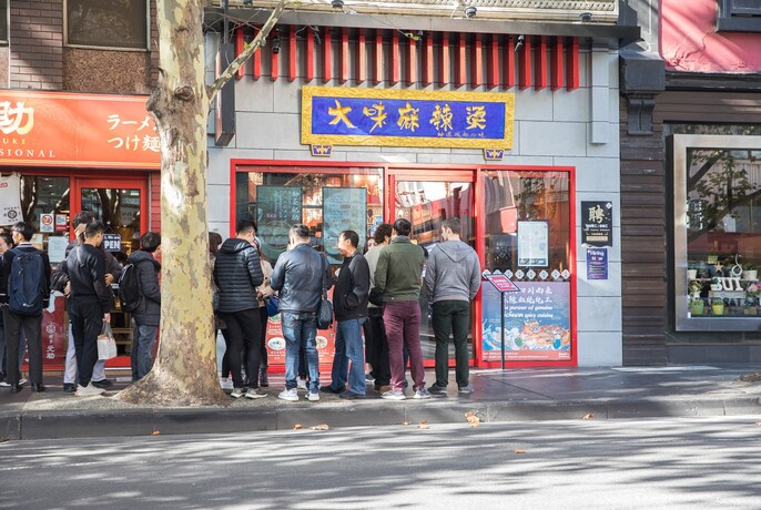 People queing in the street outside David's Spicy Pot restaurant.