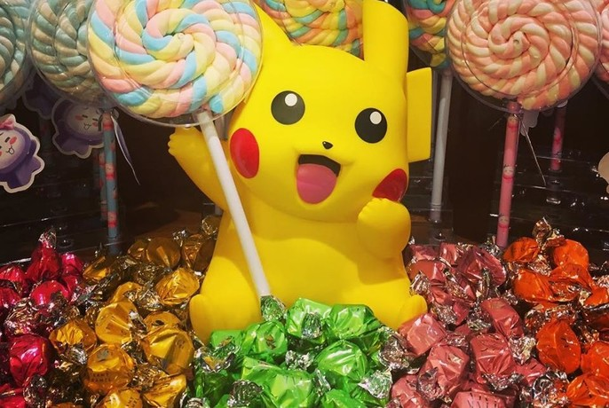 Pikachu surrounded by lollies and lollipops.