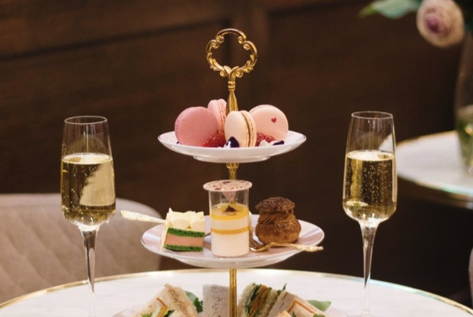 Three-tiered cake dish with cakes, biscuits and sandwiches with two glasses of champagne either side.