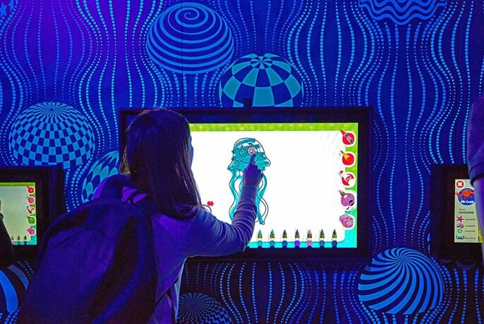Child colouring in a jellyfish drawing on a display screen.