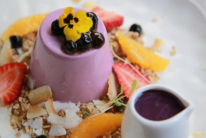 Purple dessert served with fruit and chocolate sauce.