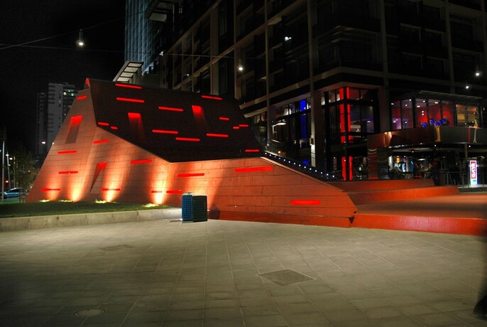 Red stair amphitheatre illuminated at night at Queensbridge Square.