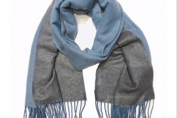 A blue and grey scarf looped together on a white background.