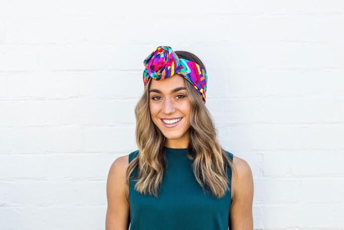 Woman with brightly-coloured headband and emerald green top.