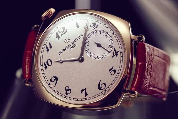 Vintage-style watch with numerals and inset seconds timer on leather strap.