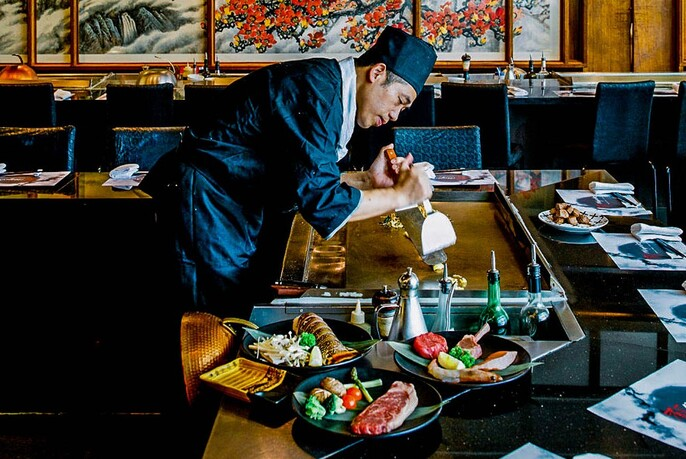 A Japanese chef tends to the teppanyaki.