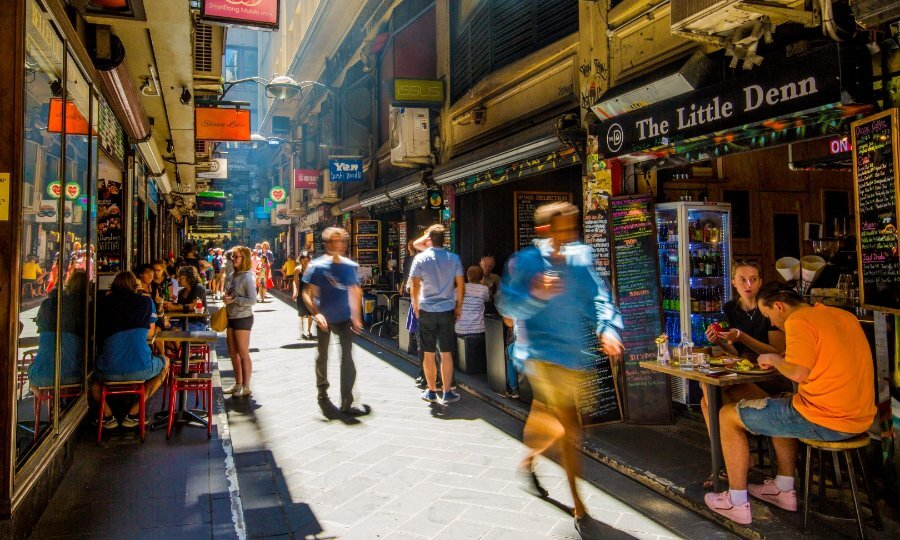 Narrow city laneway filled with shops and people eating at pavement cafes.