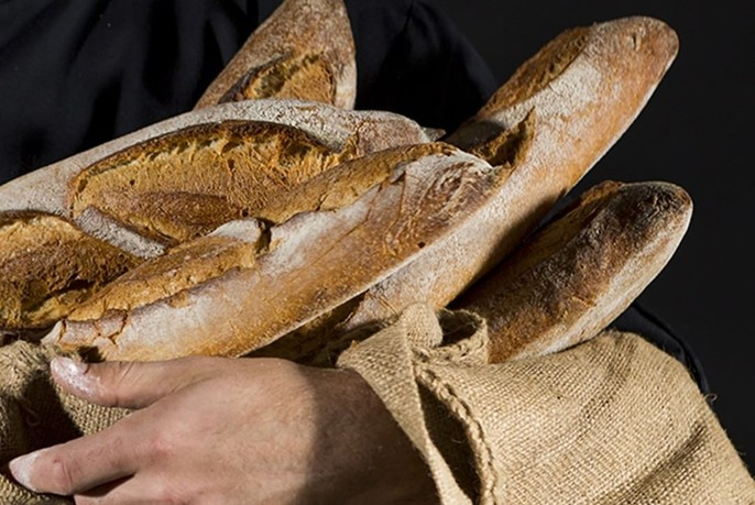 Hands holding a handful of baguette in hessian.