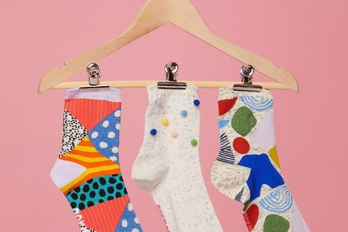 Three colourful socks on a hanger.