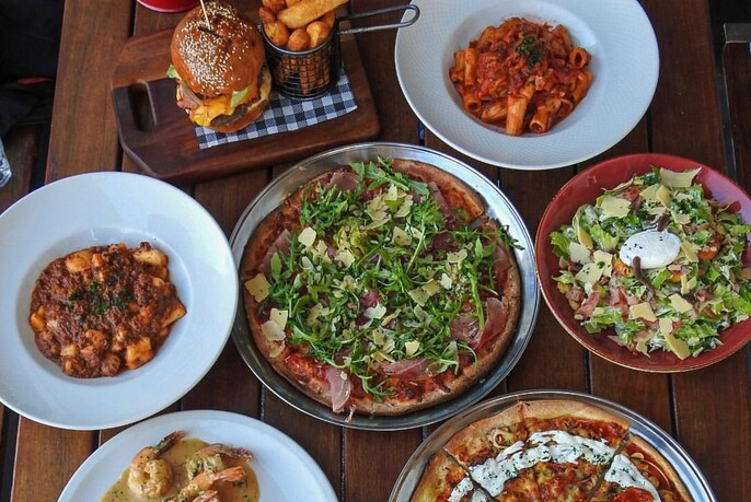 Assorted dishes on a table including hamburger with chips, pizza and salad.