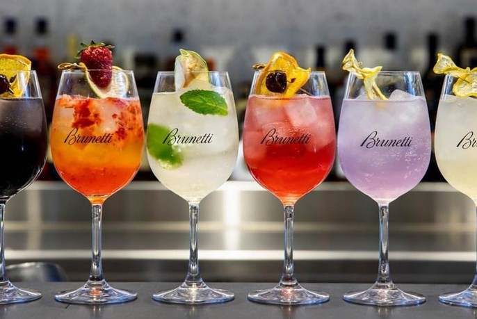 Glasses of variously-coloured drinks, all with garnishes.