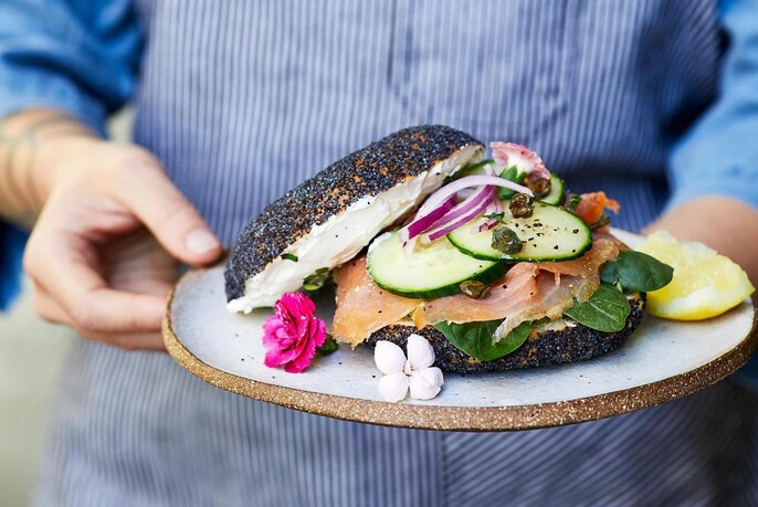 Waiter holding a rustic plate with poppyseed salmon sandwich garnished with flowers.