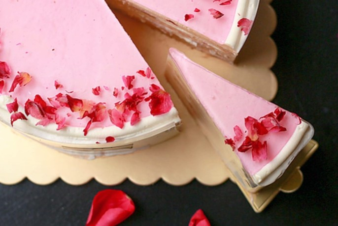 Pink cream cake with a slice cut out.
