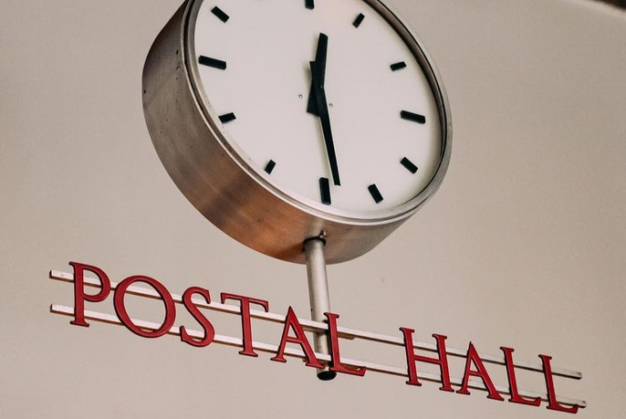 Postal Hall vintage metal sign and old post office clock.