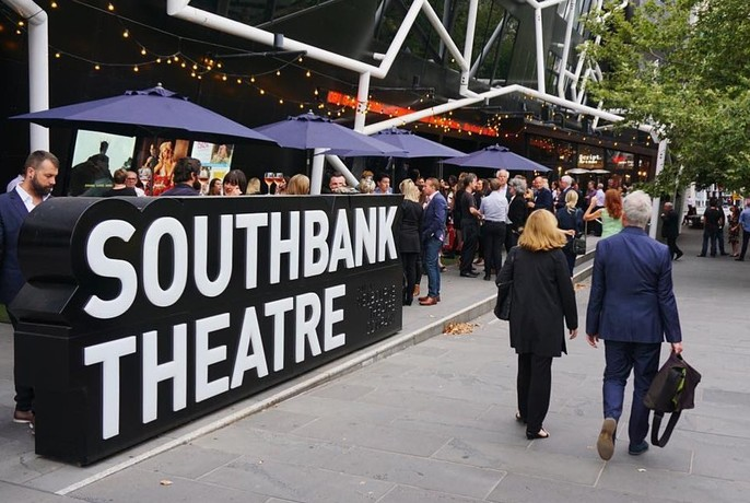 People walking past a large Southbank Theatre sign on Southbank Boulevard.