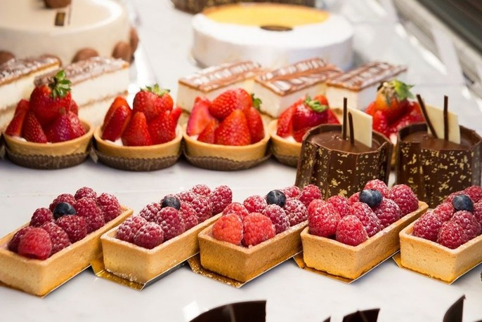 Three rows of pastries with cakes in background.