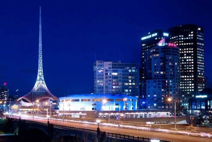 Princes Bridge and iconic spire of the Arts Centre Melbourne illuminated at night.