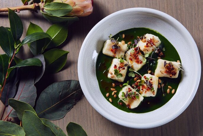 White dish of tofu in sauce with protea flower and leaves.