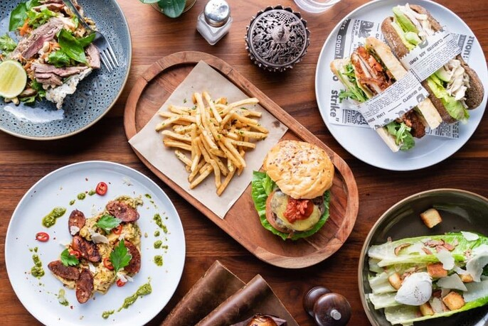 Various plates of food: salads, sandwiches and a burger and fries.