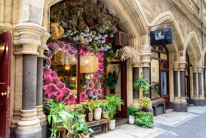 Floral window display of florist in classical Victorian stone building.