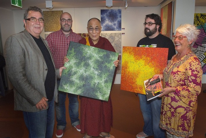 People holding Aboriginal paintings at Red Desert Dreamings gallery.