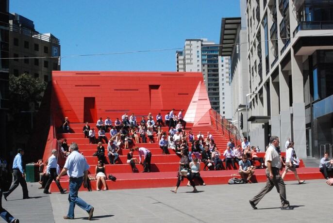 People sitting on futuristic red stair amphitheatre at Queensbridge Square.