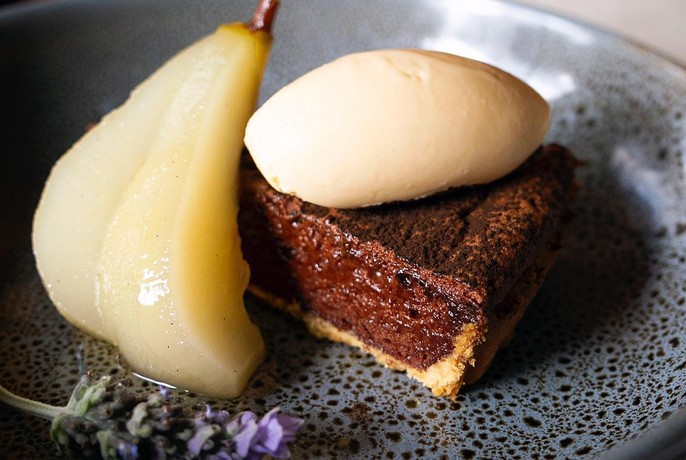 Dessert of pear, cream and chocolate cake.