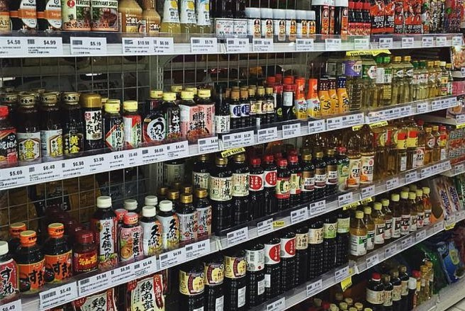 Wide range of Asian sauces and condiments lining supermarket shelves.