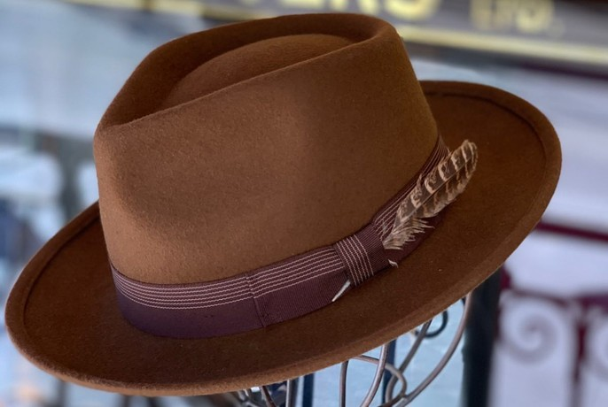 Brown Akubra-style hat with a feather in the hat band.