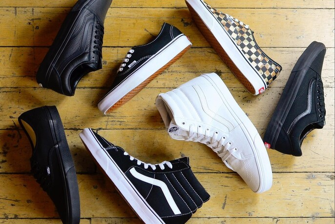 Black and white sneakers on a wooden floor.