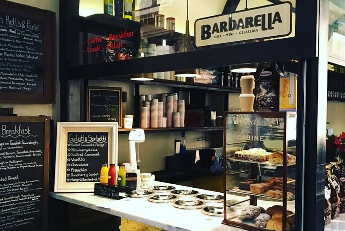 Barbarella counter with blackboard menus, signs and glass display filled with cakes, kitchen in the background.