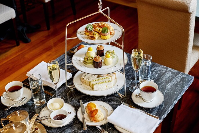 High tea selection of sweet and savoury food on three-tiered plates with cups of tea and coffee and glasses of champagne.