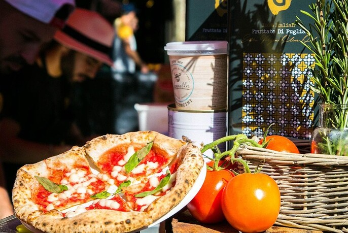 An authentic-looking margherita pizza in the sun next to a basket with ripe tomatoes and rosemary.