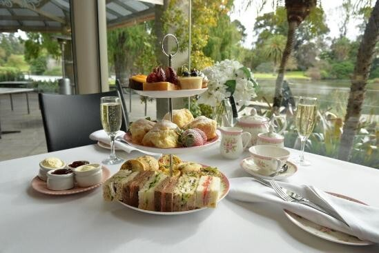 Cafe table overlooking the Botanic Gardens lake, set with sandwiches, pots of jam and cream, champagne flutes, teapot and cake stand with scones and cakes.